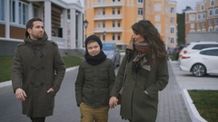 Close up of happy young family in warm clothing are walking together on the Stock Footage