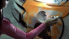 Girl gets a paint from a container on a white car body Stock Footage