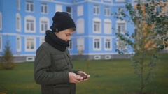 Child in warm dark grey jacket and black cap and scarf is playing phone standing Stock Footage