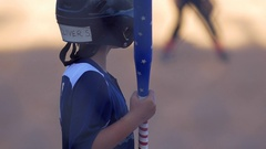 A batter playing in a boys little league baseball game with an American flag bat Stock Footage