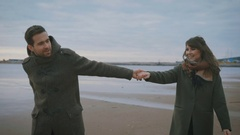 Sunny weather on a good mood. A loving couple is running along the water on the Stock Footage