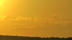 The sun sometimes hiding for clouds changes color of the sky with yellow to red. Stock Footage