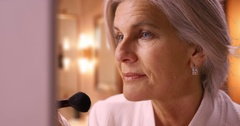 Lovely mature Caucasian woman applying makeup Stock Footage