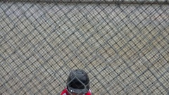 A boy practices baseball at a batting cage with a red white and blue American fl Stock Footage