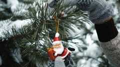 Woman decorates fir-tree with toy during new year in forest Stock Footage