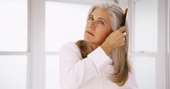 Portrait of senior Caucasian woman combing healthy hair Stock Footage