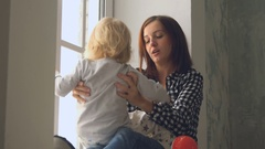 Mother plays with her little baby girl near the window Stock Footage