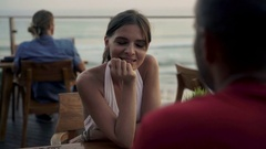 Young couple on romantic data, talking in cafe with sea view, 4K Stock Footage