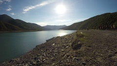 Clear sunny day and sunlit river in mountains, group of people aside riverbank Arkistovideo