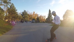 A young man longboard skateboarding downhill in a city park wearing a suit and u Stock Footage