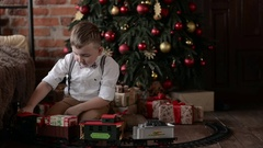 Boy playing near the Christmas tree train Stock Footage