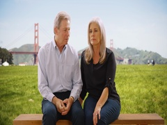 Two mid aged Caucasian people sitting on a wood bench in San Francisco Stock Footage