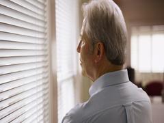 Closeup of mature Caucasian man looking through window blinds Stock Footage