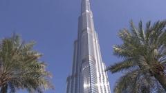 Modern Arabian architecture Burj Khalifa center seen between beautiful palm tree Stock Footage
