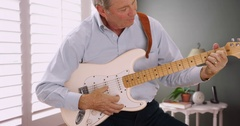 Portrait of senior male guitarist playing guitar Stock Footage