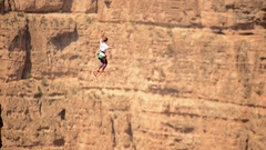 Aerial view of a woman balancing while tightrope walking and slacklining across Stock Footage