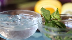 Glass bowls with ice cubes and mint leaves for preparing juice Stock Footage