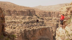 Men balance while tightrope walking and slacklining across a canyon, time-lapse. Stock Footage
