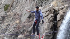 A man balances while tightrope walking and slacklining near a waterfall. Stock Footage