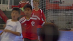 Boys celebrate a goal playing futsal youth soccer football, slow motion. Stock Footage