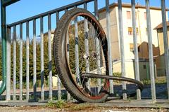 Dismounted wheels without bike attached to a city gate Stock Photos