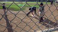 The umpire brushes off home plate at a little league baseball game, super slow m Stock Footage
