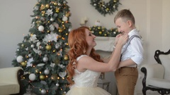 Mother dresses his son a bow tie on the background of Christmas decorations Stock Footage