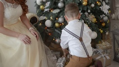 Mother and son consider  gifts on the background of Christmas decorations Stock Footage