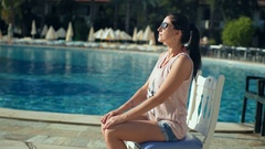 Happy woman on summer holidays relaxing near swimming pool Stock Footage