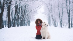 Happy young woman petting white Samoyed dog on Stock Footage