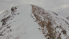Aerial view of a trail runner running to the top of a snowy mountain. Stock Footage