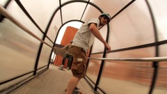 A young man does a trick on a skateboard through a tunnel. Stock Footage