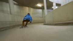 A young man rides his skateboard down a parking ramp. Stock Footage