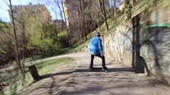 A young man does some tricks on a skateboard while riding down a hill, time-laps Stock Footage