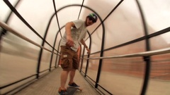 A young man does a trick on a skateboard through a tunnel, time-lapse. Stock Footage