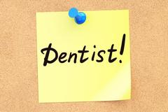 Dentist! Text on a sticky note pinned to a corkboard. 3D rendering Stock Illustration