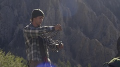Rock Climber Gathers And Coils Climbing Rope Around His Shoulders (Slow Motion) Stock Footage