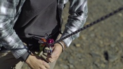 Man Belays His Climbing Partner, Closeup Of His Hands Pulling On Climbing Rope Stock Footage