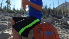 A boy hiking on a trail in the mountains takes a break to drink water. Stock Footage