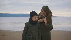 Close up of mother and son in warm clothes standing on the shore together with Stock Footage