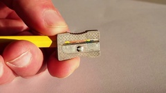 Pinning yellow color pencil using a metal pencil sharpener Stock Footage
