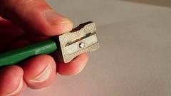 Pinning agreen color pencilusingametalpencil sharpener Stock Footage