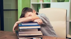 Little boy sleeping on a pile of books Stock Footage