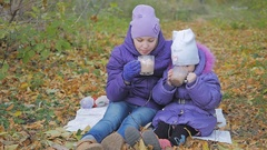 Two little sisters in the autumn park drinking cocoa with marmalade. slow-motion Stock Footage