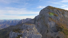 Aerial view of a man balancing while slacklining on a tightrope in the mountains Stock Footage