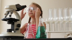 Caucasian girl using microscope and experimenting with liquid Stock Footage