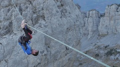 A man tries to balance while slacklining on a tightrope in the mountains. Stock Footage