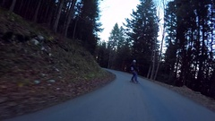 POV of young men longboard skateboarding downhill on a rural road avoiding a car Stock Footage