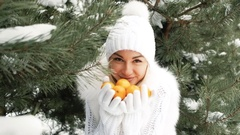 Lovely woman offers tangerines against background of winter landscape Stock Footage