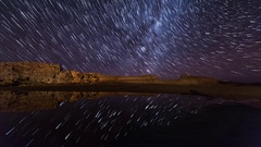 Star trails at night followed by a moonrise reflected over water Stock Footage
